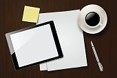 Dark wooden office desk with sheets of paper, digital tablet with blank screen, yellow sticky note, cup of coffee and silver pen.