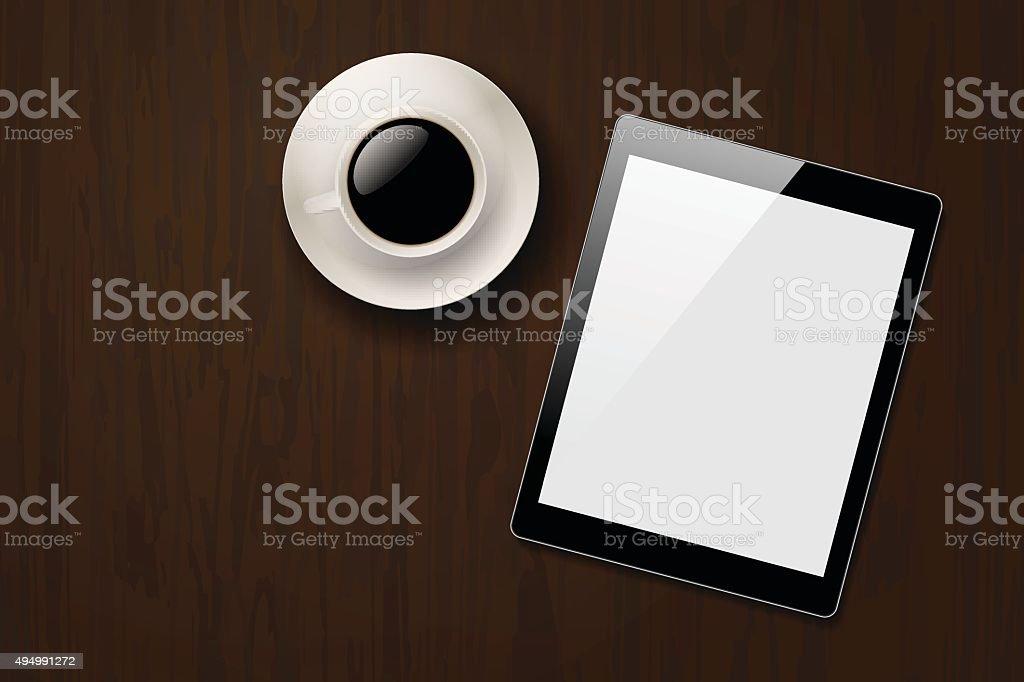 Tablette numérique et tasse de café sur le bureau en bois sombre