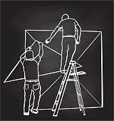 Two men setting up a display