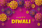 Diwali festival of lights holiday typographic design with hanging paper cut style of Indian Rangoli. Purple color background. Vector illustration.