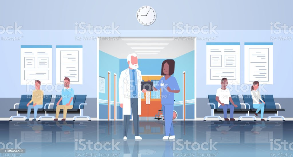 doctor and nurse discussing in hospital waiting hall corridor over...