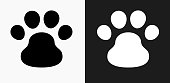 Dog Paw Icon on Black and White Vector Backgrounds. This vector illustration includes two variations of the icon one in black on a light background on the left and another version in white on a dark background positioned on the right. The vector icon is simple yet elegant and can be used in a variety of ways including website or mobile application icon. This royalty free image is 100% vector based and all design elements can be scaled to any size.