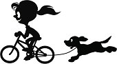 A silhouette girl on a bicycle with her dog tethered and running behind.