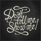 """""""Don't Tell Me, Show Me"""" quote on the blackboard background"""