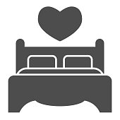 Double bed and pillows solid icon. Bedding furniture with heart shape symbol, glyph style pictogram on white background. Valentines day sign for mobile concept, web design. Vector graphics