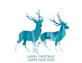 Double Exposure Christmas Card with blue winter forest inside the shape. The text says Merry Christmas and Happy New year.  Reindeer Pair