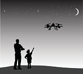 A vector silhouette illustration of an adult man and his young son playing with a remote controlled flying drone in a field against a dark grey night sky with stars and a crescent moon.