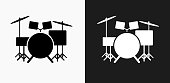 Drums Instrument Icon on Black and White Vector Backgrounds. This vector illustration includes two variations of the icon one in black on a light background on the left and another version in white on a dark background positioned on the right. The vector icon is simple yet elegant and can be used in a variety of ways including website or mobile application icon. This royalty free image is 100% vector based and all design elements can be scaled to any size.