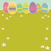 Colorful vector illustration of Easter eggs over grass background.