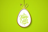 Easter celebrate banner with golden easter egg and handwritten holiday wishes of a Happy Easter on green background. Vector illustration.