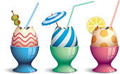 Three eggcups with eggs and drink straws.