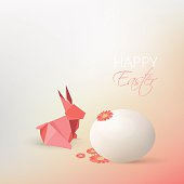 Easter egg, gerbera flowers and pink origami rabbit decoration isolated on soft subtle blurry background