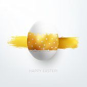 White egg carelessly painted by one horizontal line on gold.  Light and shadows and 3D realistic round object give original and beautiful golden color shimmering. Dots pattern on egg.  Easter wishing card design. Photorealistic 3D space with gentle light and soft shadows.  Zoom to see the details. Vector file.