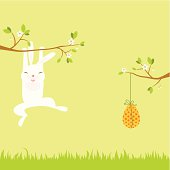 White rabbit is hanging on the tree branch and trying to get an Easter egg on the opposite branch. Easy edited (elements are on different layers and global colors) with copy space.