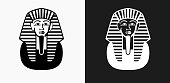 Egyptian Coffin Icon on Black and White Vector Backgrounds. This vector illustration includes two variations of the icon one in black on a light background on the left and another version in white on a dark background positioned on the right. The vector icon is simple yet elegant and can be used in a variety of ways including website or mobile application icon. This royalty free image is 100% vector based and all design elements can be scaled to any size.