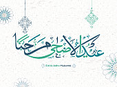 Eid Al Adha Mubarak text in Arabic calligraphic style on Islamic seamless pattern background decorated with hanging ornamental elements.