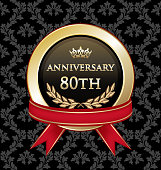Eightieth anniversary celebration gold award with with a red ribbon on a black damask background.