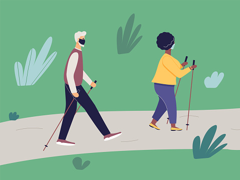 Elderly fit man and african woman engaged in Nordic walking with sticks on  path in park