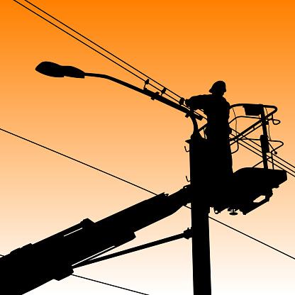 Electrician on platform fixing streetlight in silhouette