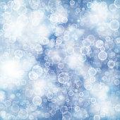 Flying out of focus light on a blue blurred background. Vector defocused illustration