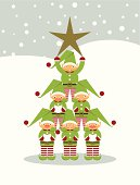 Group of happy elves singing and making a christmas tree-shaped tower.