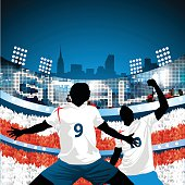 Two silhouetted English soccer players celebrating after scoring a goal with a giant lcd flashing goal above the stadium and the crowd forming a huge English flag behind them.
