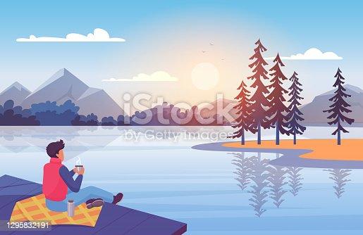 istock Enjoy nature at sunset, young man sitting on wooden pier, enjoying natural landscape 1295832191