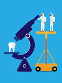 Two dental professionals in protective gear stand on a platform to view a tooth through a microscope.