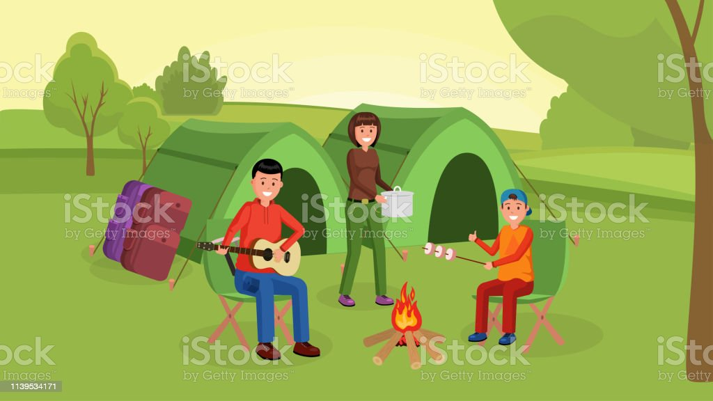 Parents with son sitting near campfire and eating marshmallows....