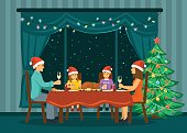 Family sitting in living room at home in front of big window with night stars behind, celebrating merry christmas and happy new year