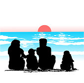 Family sitting by the ocean and watching the sunset