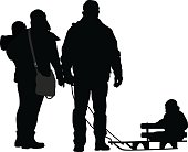 A vector silhouette illustration of a family dressed in heavy winter clothes outside.  The mother holds a young child in her arms while the father holds the reigns on a sled riden by another small child.