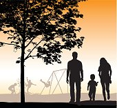 A vector silhouette illustration of a family walking through a park indluding a mother, father, and young son.  The walk by a tree in front of a playground with young boys playing in leaves and on a swingset.  The sky is an orange gradient despicting dusk.