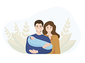 Family with a newborn child. The father holds a small child in his arms, the mother stands beside him. The concept of family values, motherhood and paternity . background of the leaves with nature