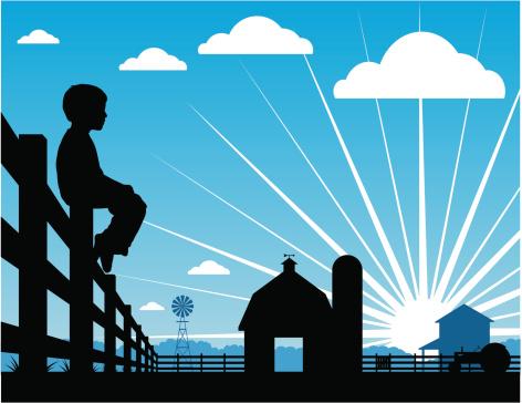 Farm boy silhouetted sitting on a fence
