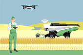 Farmer controls an autonomous combine harvester via drone. Internet of things in agriculture