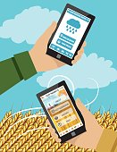 Farmers Hands Holds a Tablet With an Agriculture Application On It. There is a farm and field in the background.