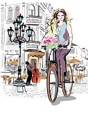 Fashion girl rides a bicycle the streets of the old town. Hand drawn illustration. Street musician and street cafe. Retro style.