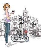 Fashion young girl drinking coffee in the street of old city. Romantic bycicle.
