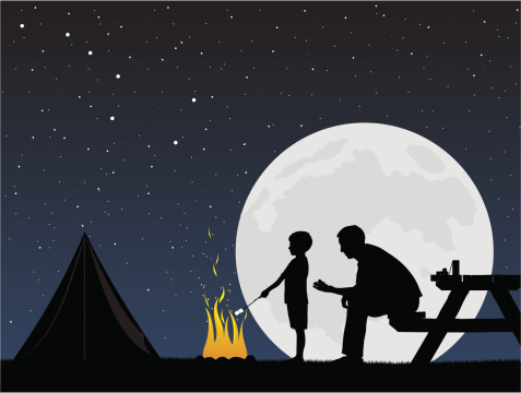 Father and son camping around campfire