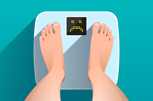 Feet of woman standing on bathroom scales with unhappy face on display