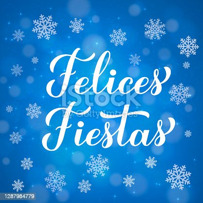 istock Felices Fiestas calligraphy hand lettering on blue background with bokeh and snowflakes.. Happy Holidays in Spanish. Christmas typography poster. Vector template for greeting card, banner, flyer. 1287984779