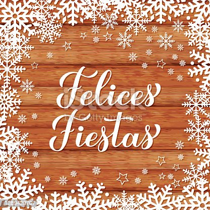 istock Felices Fiestas calligraphy hand lettering on wood background with snowflakes. Happy Holidays in Spanish. Christmas typography poster. Vector template for greeting card, banner, flyer, etc 1289429707