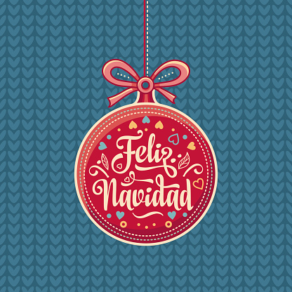 Feliz Navidad.  Red Christmas ball with good wishes in Spanish.