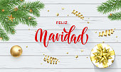 Feliz Navidad Spanish Merry Christmas golden decoration and calligraphy font on white wooden background for greeting card. Vector Christmas or New Year gold shiny star on Xmas tree for winter holiday