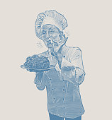 Female chef serving chicken and giving okay hand sign