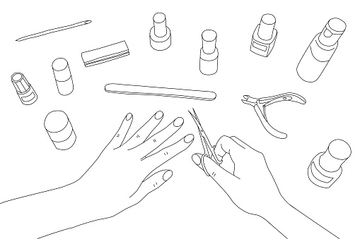 Female hands coloring nails manicure surrounded by tools and cosmetics for nail care, top view.