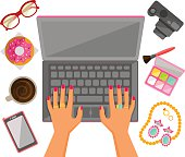 Female hands typing on a laptop with trendy items around