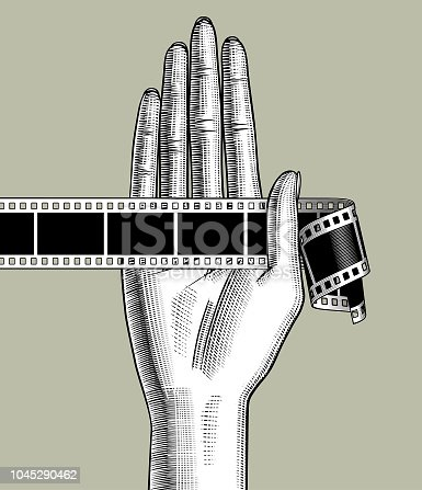 Female palm hand holding a camera roll. Vintage engraving stylized drawing. Vector illustration
