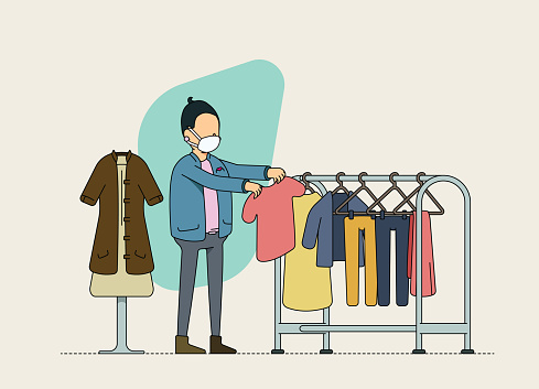 Female second hand clothing store owner checking inventory. Sustainable retailing and product up-cycling. Adjusting to the new normal and social distancing norms, wearing mask at work.